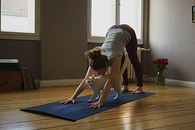 Full length of woman practicing downward facing dog position with cat on exercise mat at home - p301m1579784 by Halfdark