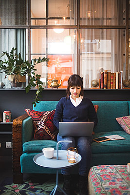 Full length of confident female professional using laptop sitting on sofa at office - p426m2089010 by Maskot
