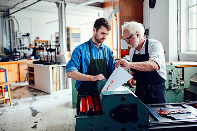 Senior craftsman/technician supervising young man on letterpress machine in book arts workshop - p429m1181343 by Alys Tomlinson
