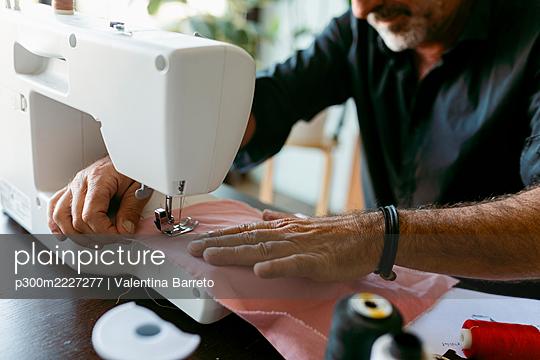 Male costume designer sewing fabric while working in studio - p300m2227277 by Valentina Barreto