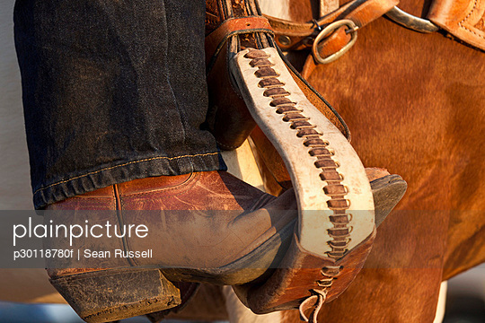 A cowboy boot in a horse stirrup, detail - p30118780f by Sean Russell