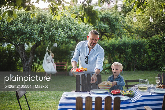 Mature father directing son with food plate while pointing at table in yard - p426m2135584 by Maskot
