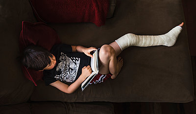High angle view of boy with broken leg reading book while lying on sofa at home - p1166m2011871 by Cavan Images