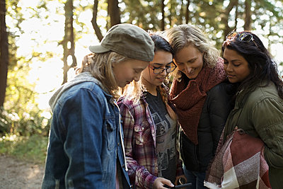 Lesbian parents with daughters checking GPS, hiking in woods - p1192m1511895 by Hero Images