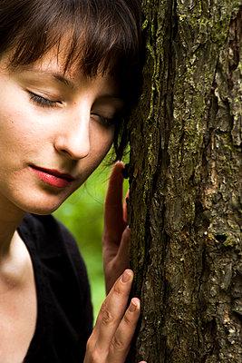 Junge Frau an Baum gelehnt - p1611m2182312 von Bernd Lucka