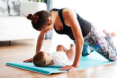 Mother with baby exercising on yoga mat at home - p300m1581669 by gpointstudio