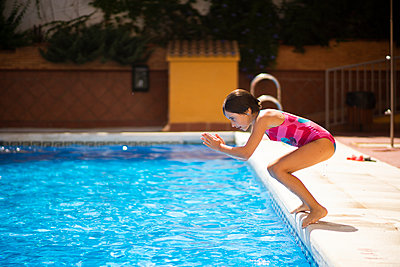 Young girl jumping head first into the pool in summer - p300m2029493 by Javier Sánchez Mingorance
