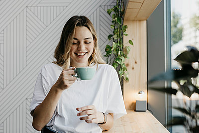 Smiling young woman holding coffee cup while standing in cafe - p300m2226032 by letizia haessig photography