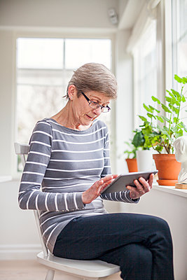 Senior woman using digital tablet - p312m1407447 by Malin Kihlstrom