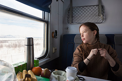Woman sitting at table on train - p352m2120452 by Gustaf Emanuelsson