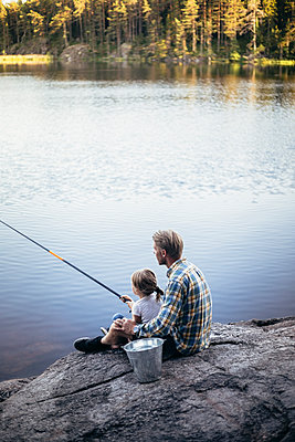 Father and daughter fishing while sitting by lake - p426m2212179 by Maskot
