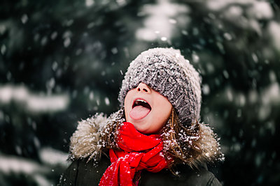 Portrait of girl catching falling snow on tongue - p429m1547833 by Rebecca Nelson