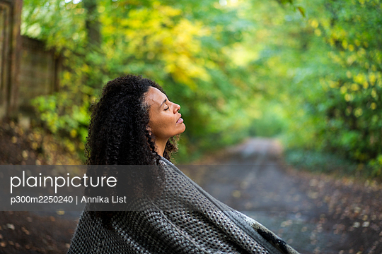 Curly hair woman wearing jacket sitting with eyes closed on footpath in forest - p300m2250240 by Annika List