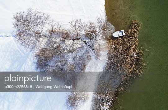 Boat moored at Irrsee by snow covered land during winter - p300m2256818 by Wolfgang Weinhäupl