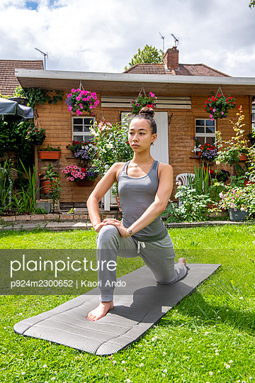 UK, London, Woman exercising on lawn in front of house - p924m2300652 by Kaori Ando