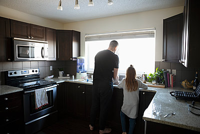 Father and daughter doing dishes at kitchen sink - p1192m1567397 by Hero Images