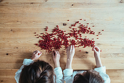 Children playing with cranberries on a wooden table - p1414m2044896 by Dasha Pears