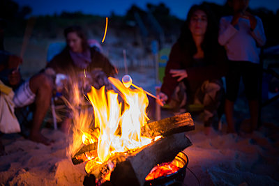 toasting marshmallows at the beach - p1424m1500965 by Julia Cumes