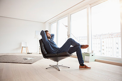 Young man relaxing on leather chair in his living room - p300m1047750f by Rainer Berg