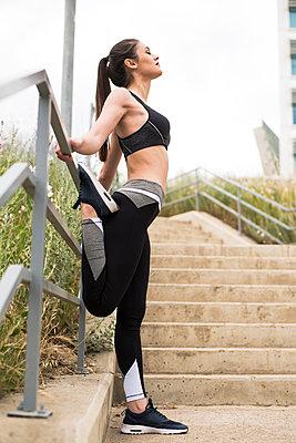 Sportive woman stretching leg - p300m2004465 by Aitor Carrera Porté