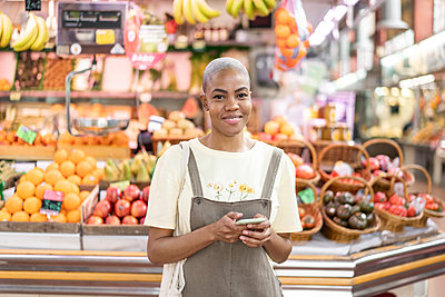 Portrait of smiling woman buying groceries in a market hall - p300m2179889 by VITTA GALLERY