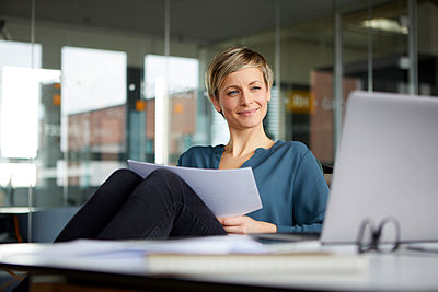 Smiling businesswoman working at desk in office - p300m2181091 by Rainer Berg