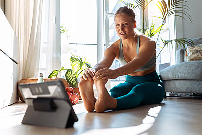 Woman with digital tablet stretching while exercising at home - p300m2256006 by Josep Suria