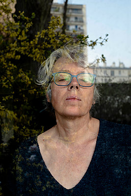 Grey-haired woman looking out of window - p445m2173644 by Marie Docher