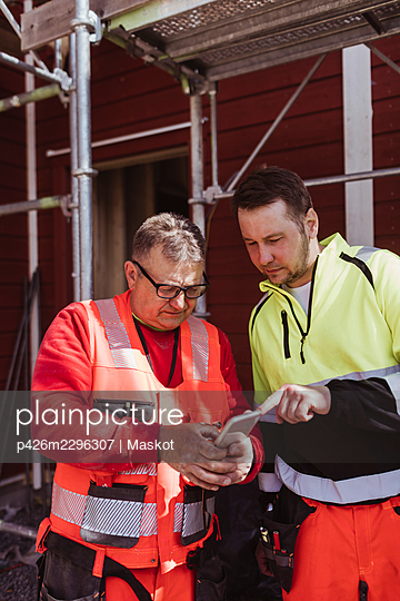 Mature male construction worker discussing over smart phone with colleague at construction site - p426m2296307 by Maskot