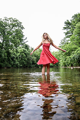 Girl In Red Dress in Stream - p1019m2100422 by Stephen Carroll