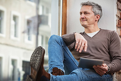 Caucasian man with digital tablet looking through window while sitting at home - p300m2274048 by Studio 27