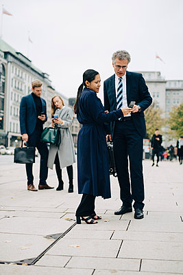 Female and male entrepreneurs using smart phone while standing on street in city - p426m2186953 by Maskot