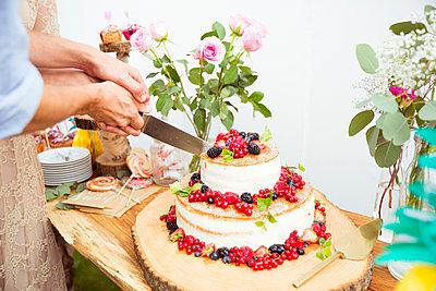 Brautpaar schneidet Hochzeitstorte an - p432m2007504 von mia takahara