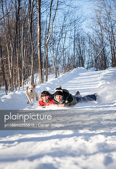 Father and son sledding down a snowy hill together on winter day. - p1166m2255818 by Cavan Images