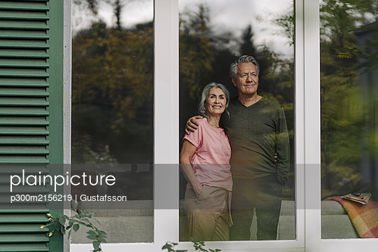 Senior couple behind windowpane of their home looking out - p300m2156219 by Gustafsson