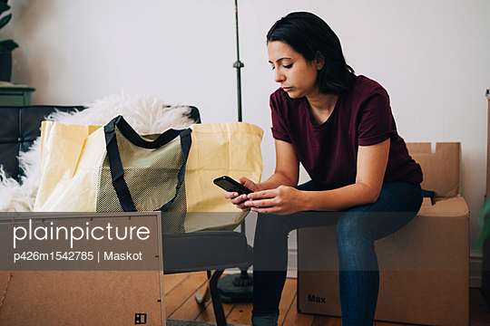 Mid adult woman using mobile phone while sitting on box against wall - p426m1542785 by Maskot