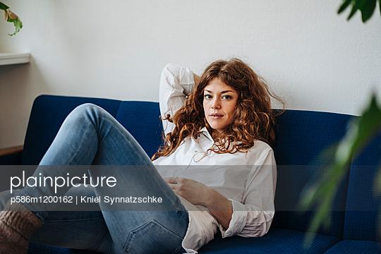 Junge Frau mit roten Haaren auf dem Sofa - p586m1200162 von Kniel Synnatzschke