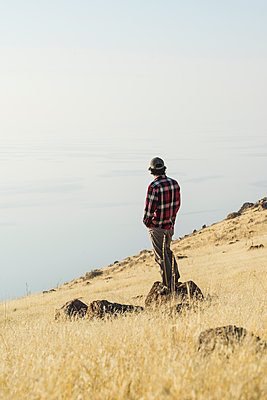 Side view of man looking at sea while standing on rock against sky - p1166m1530765 by Cavan Images