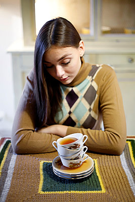 Young woman in retro sweater and cups of tea - p1521m2128938 by Charlotte Zobel