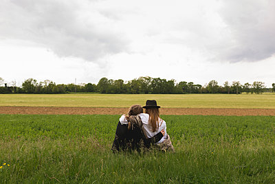 Back view of two friends sitting on a meadow at countryside - p300m1156828 by Boy photography