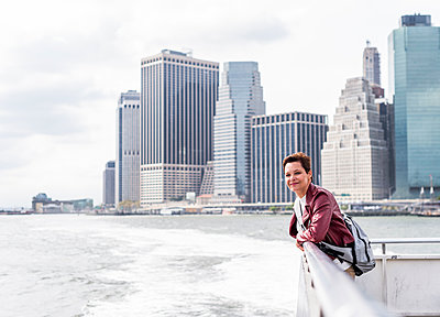USA, New York City, woman on ferry with Manhattan skyline in background - p300m1449778 by Uwe Umstätter