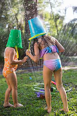 Girls with buckets on head playing with garden sprinkler - p924m1468950 by Kinzie Riehm