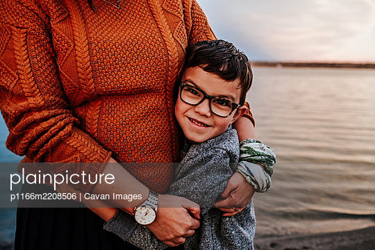 Happy young boy hugging mom near a lake on a autumn evening - p1166m2208506 by Cavan Images