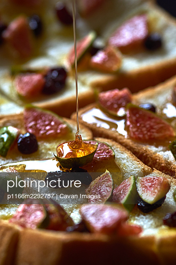 Close-up view pouring honey on the figs and bread - p1166m2292787 by Cavan Images