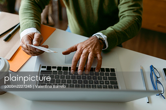 Midsection of man using credit card while working on laptop at home - p300m2227245 by Valentina Barreto