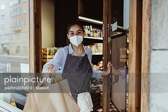 Portrait of female owner with take away food at doorway of delicatessen shop - p426m2270510 by Maskot