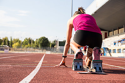 Female runner on tartan track in starting position - p300m1191688 by Andrés Benitez