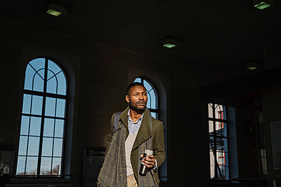Stylish man with reusable cup getting out of the train station - p300m2154581 by Hernandez and Sorokina