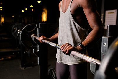 Young man preparing to lift barbell while exercising in gym - p300m2273619 by Antonio Ovejero Diaz