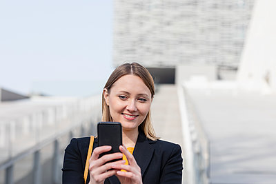 Mid adult businessman smiling while taking selfie through mobile phone - p300m2274312 by Emma Innocenti